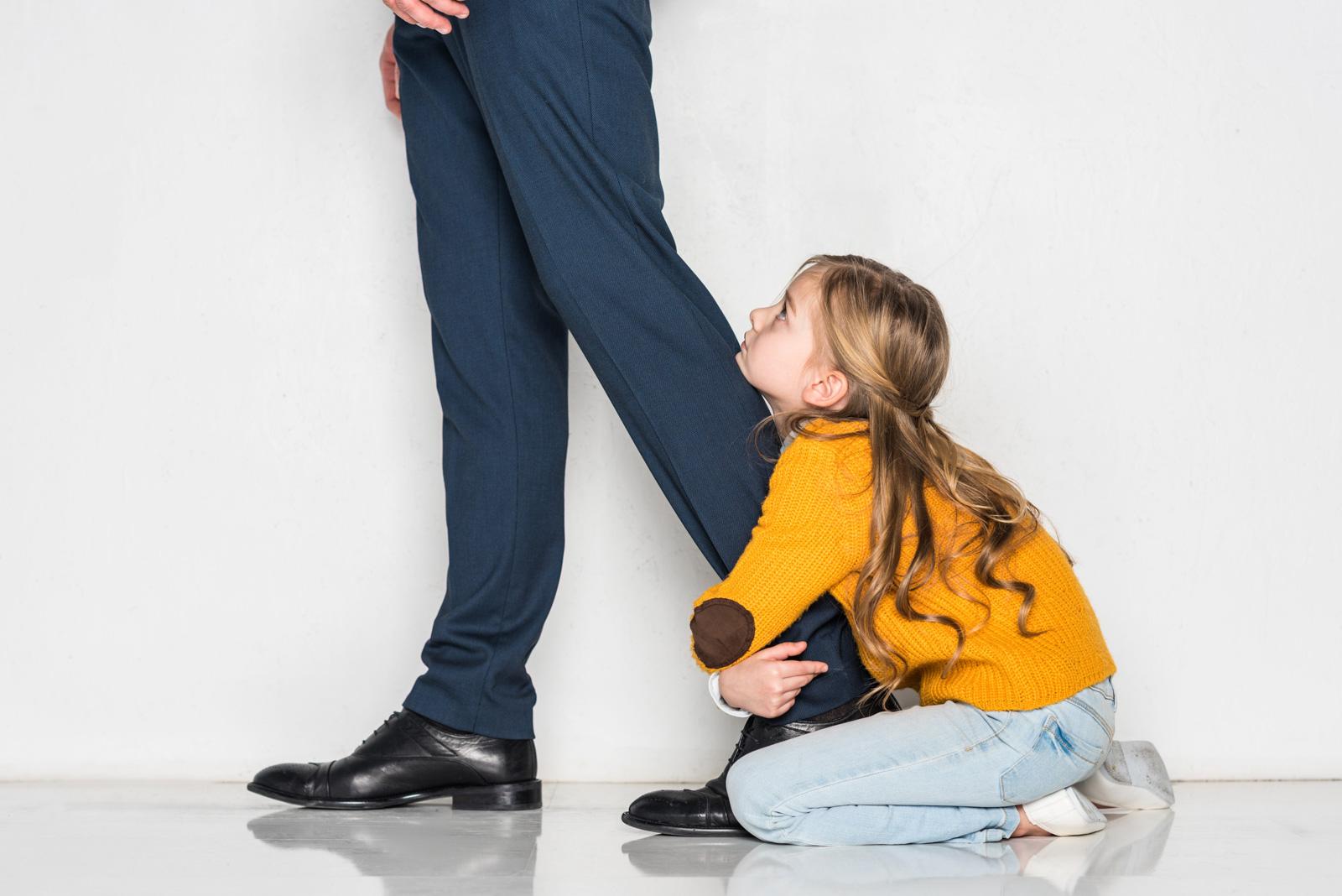 girl holding dad pant leg